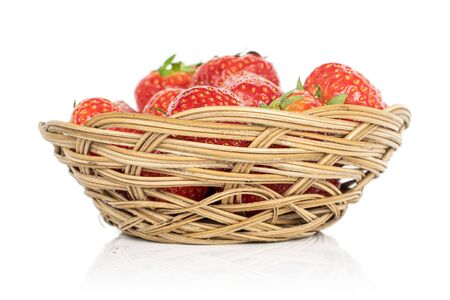 Lot of whole fresh red strawberry in round rattan bowl isolated on white background Stock Photo
