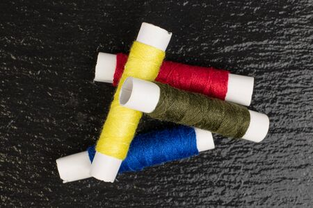 Group of four whole sewing thread spool heap flatlay on grey stone Stock Photo