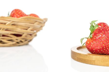 Lot of whole fresh red strawberry in round rattan bowl on round bamboo coaster isolated on white background Stock Photo
