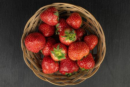 Lot of whole fresh red strawberry in round rattan bowl flatlay on grey stone