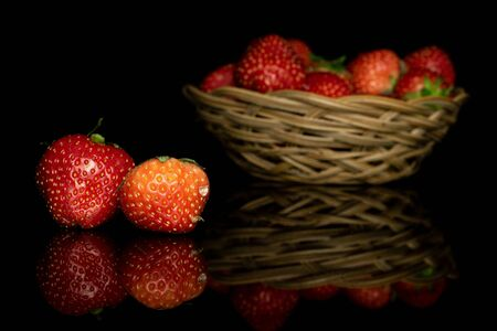 Lot of whole fresh red strawberry two in focus in round rattan bowl isolated on black glass