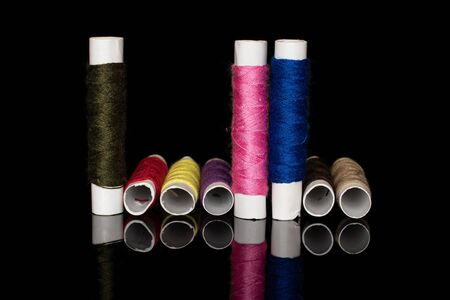 Group of eight whole colorful sewing thread spool upright isolated on black glass