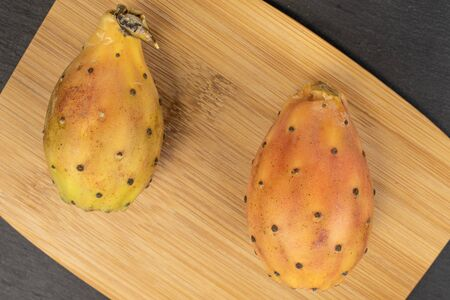 Group of two whole prickly green opuntia on bamboo cutting board flatlay on grey stone