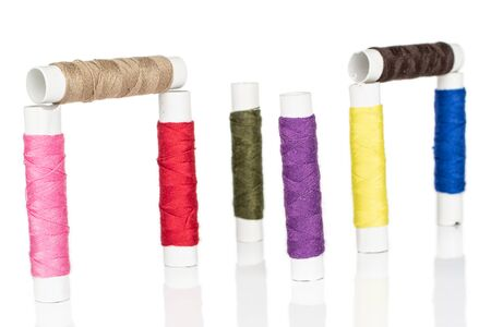 Group of eight whole upright sewing thread spool isolated on white background