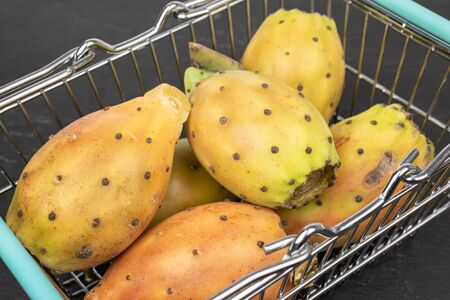 Group of six whole prickly green opuntia heap in shopping basket on grey stone