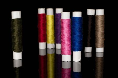 Group of eight whole upright sewing thread spool isolated on black glass 写真素材