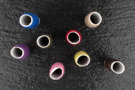 Group of eight whole sewing thread spool flatlay on grey stone