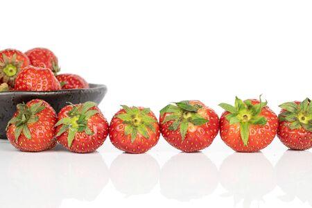 Dużo całych świeżych czerwonych truskawek w rzędzie w przeszklonej misce na białym tle