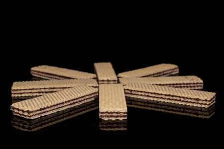 Group of eight whole sweet chocolate biscuit wafer isolated on black glass