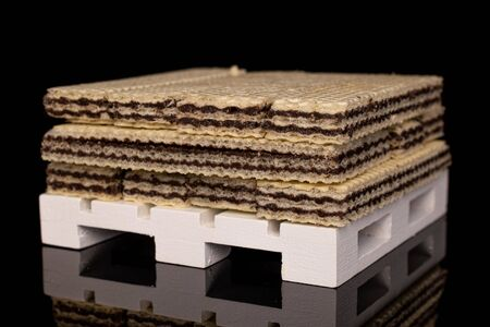 Lot of whole sweet chocolate biscuit wafer on white pallet isolated on black glass