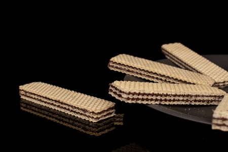Group of five whole sweet chocolate biscuit wafer on gray ceramic plate isolated on black glass