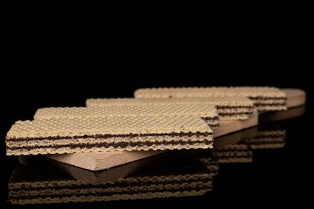 Group of four whole sweet chocolate biscuit wafer on wooden cutting board isolated on black glass Banque d'images