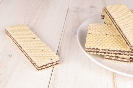 Lot of whole sweet chocolate biscuit wafer on white ceramic plate on white wood