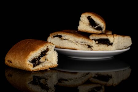 Group of four whole sweet czech bun on white ceramic plate isolated on black glass