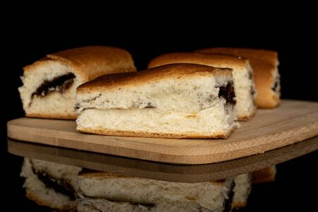 Group of four whole sweet czech bun on bamboo cutting board isolated on black glass