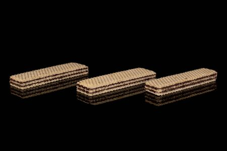 Group of three whole sweet chocolate biscuit wafer isolated on black glass