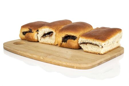Group of four whole sweet czech bun on bamboo cutting board isolated on white background