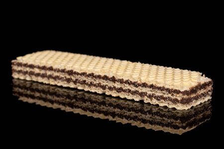 One whole sweet chocolate biscuit wafer isolated on black glass