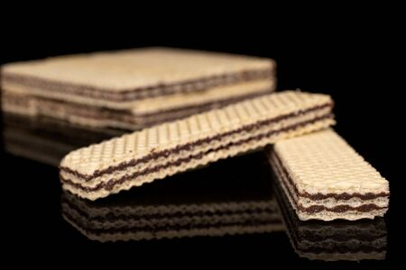 Lot of whole sweet chocolate biscuit wafer two in focus isolated on black glass