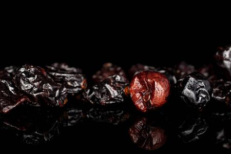 Lot of whole dried cowberry isolated on black glass