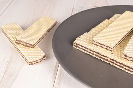Lot of whole sweet chocolate biscuit wafer on gray ceramic plate on white wood