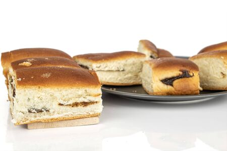 Lot of whole baked sweet czech bun on gray ceramic plate isolated on white background
