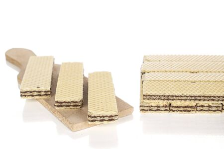 Lot of whole sweet chocolate biscuit wafer on wooden cutting board isolated on white background