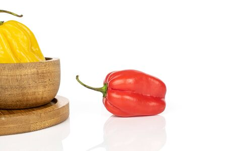Group of two whole hot chili habanero on round bamboo coaster in bamboo bowl isolated on white background