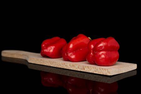 Group of three whole hot chili habanero on wooden cutting board isolated on black glass