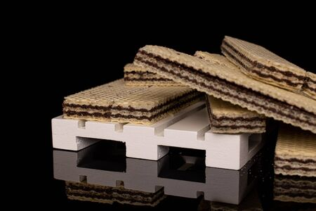 Lot of whole disordered sweet chocolate biscuit wafer on white pallet isolated on black glass Banque d'images