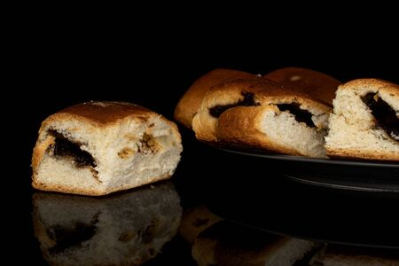 Group of four whole sweet czech bun one in focus on gray ceramic plate isolated on black glass
