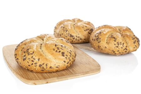 Group of three whole sesame kaiser roll on bamboo cutting board on wooden cutting board isolated on white background Stock fotó