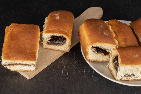 Group of six whole sweet czech bun on white ceramic plate on wooden cutting board on grey stone Stock fotó