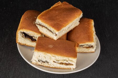 Group of five whole sweet czech bun on white ceramic plate on grey stone