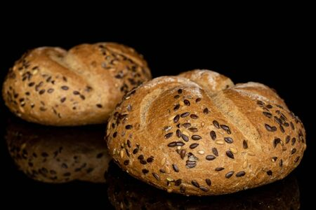 Group of two whole sesame kaiser roll isolated on black glass