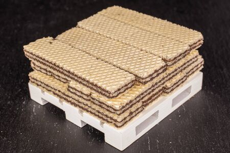 Lot of whole sweet chocolate biscuit wafer on white pallet on grey stone
