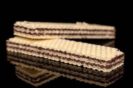 Group of two whole sweet chocolate biscuit wafer isolated on black glass