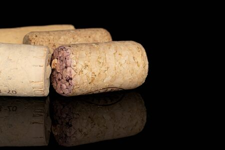 Lot of whole common wine cork isolated on black glass
