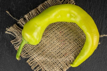 One whole hot green pepper banana with jute fabric flatlay on grey stone Banco de Imagens