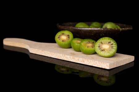 Group of lot of whole four halves of hardy green kiwi on wooden cutting board in glazed bowl isolated on black glass