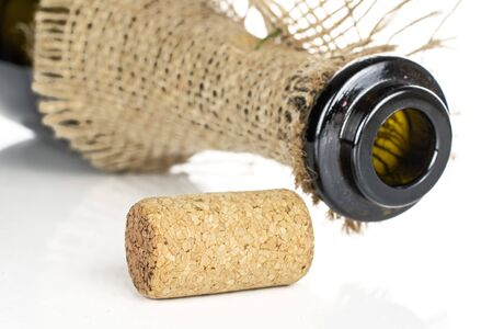 One whole common wine cork closeup  with glass bottle with jute fabric isolated on white background