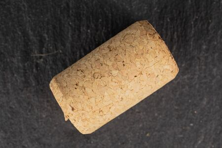 One whole common wine cork flatlay on grey stone Reklamní fotografie