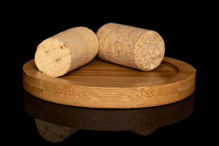 Group of two whole common wine cork on round bamboo coaster isolated on black glass Stock fotó
