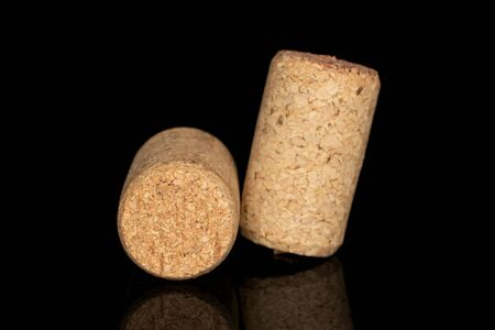 Group of two whole common wine cork isolated on black glass