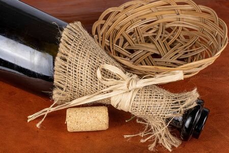One common wine cork with glass bottle tied by jute with rope and rattan bowl on cognac leather Reklamní fotografie
