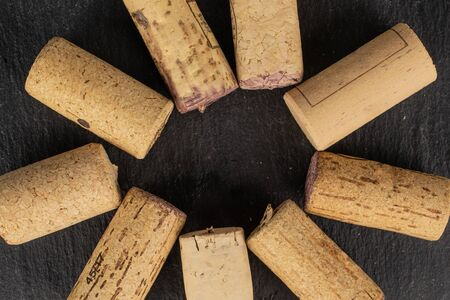 Lot of whole common wine cork circle flatlay on grey stone