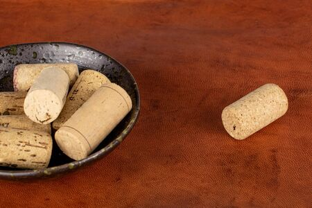 Lot of whole common wine cork in glazed bowl on cognac leather