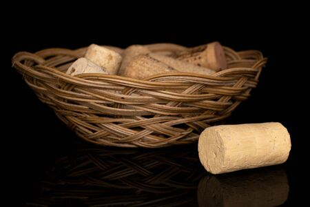 Lot of whole common wine cork in round rattan bowl isolated on black glass