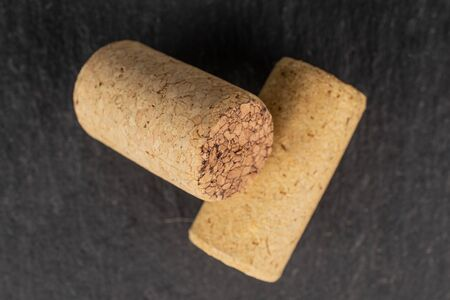 Group of two whole common wine cork flatlay on grey stone
