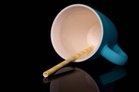 One whole paper straw with blue ceramic cup isolated on black glass Reklamní fotografie